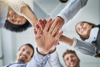 Buy stock photo Low angle shot of a group of businesspeople joining their hands in a huddle in an office