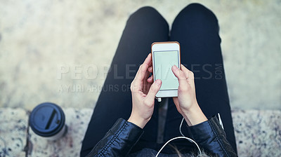 Buy stock photo Cropped shot of a woman using a mobile phone in the city