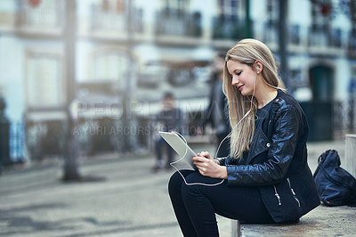 Buy stock photo Shot of an attractive woman using a digital tablet and earphones in the city