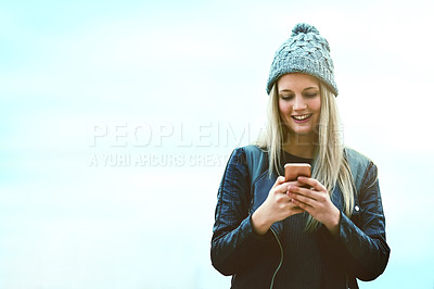 Buy stock photo Shot of an attractive young woman using a mobile phone outdoors