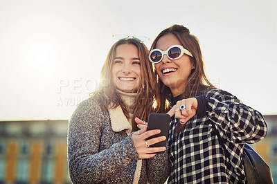 Buy stock photo Cropped shot of two attractive young women spending a day in the city