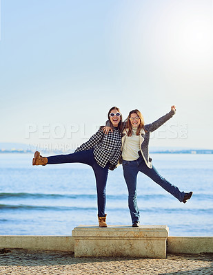 Buy stock photo Full length portrait of two attractive young women spending a day by the ocean