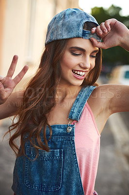 Buy stock photo Shot of an attractive young woman posing with a cap on and showing the peace sign outside during the day