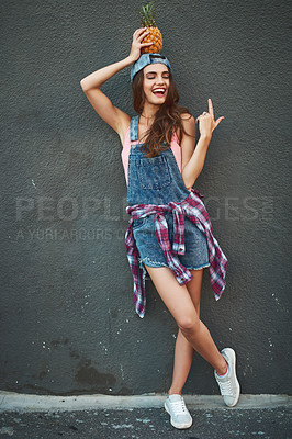 Buy stock photo Shot of a cheerful young woman holding a pineapple on her head while standing against a grey background