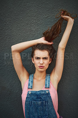 Buy stock photo Portrait of a carefree young woman holding her hair up while standing against a grey background