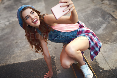 Buy stock photo Shot of a carefree young woman riding low on a skateboard while taking a self portrait with her cellphone outside during the day