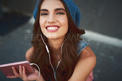 Buy stock photo Portrait of a carefree young woman seated on the floor while listening to music through her earphones outside during the day