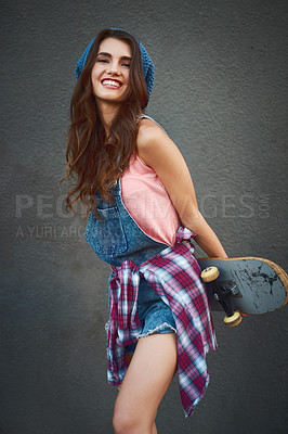 Buy stock photo Shot of an attractive young female skater holding a skateboard behind her back while standing against a grey background