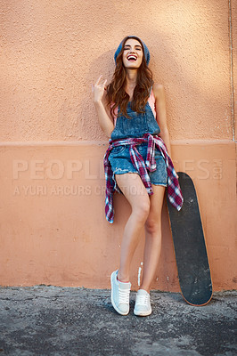 Buy stock photo Portrait of a carefree young woman standing with her skateboard against a orange background