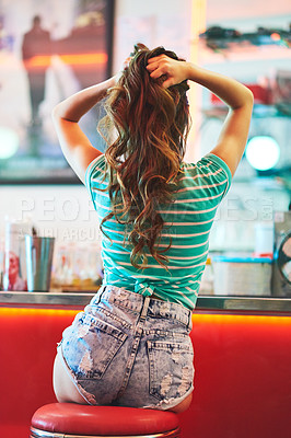 Buy stock photo Rearview shot of an unrecognizable woman holding her hair up in a diner