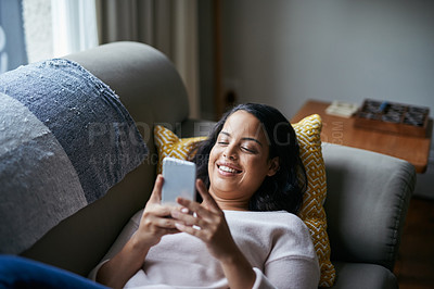 Buy stock photo Shot of an attractive young woman using a cellphone at home