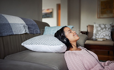 Buy stock photo Shot of an attractive young woman listening to music at home