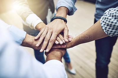 Buy stock photo Shot of a group of unrecognizable work colleagues forming a huddle with their hands outside during the day