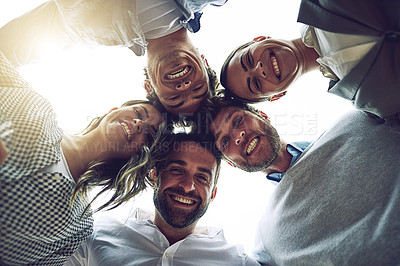 Buy stock photo Low angle portrait of a group of cheerful young work colleagues standing in a circle and looking down outside during the day