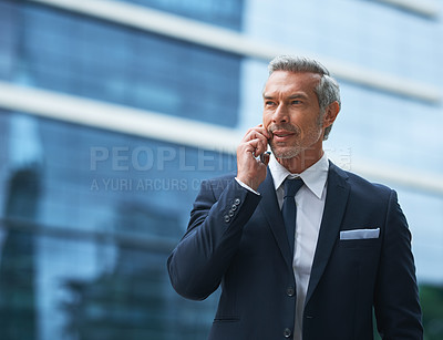 Buy stock photo Shot of a handsome mature businessman in corporate attire on a call outside during the day
