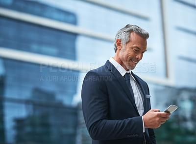Buy stock photo Shot of a handsome mature businessman in corporate attire using a cellphone outside during the day
