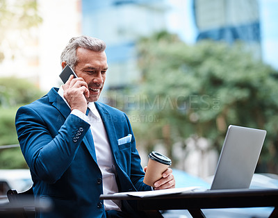 Buy stock photo Shot of a handsome mature businessman in corporate attire on a call and using a laptop outside during the day