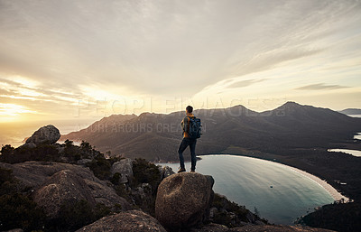 Buy stock photo Rearview shot of a young man taking in the view while standing on a mountain peak