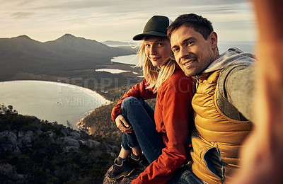 Buy stock photo Cropped portrait of an affectionate young couple taking selfies while sitting on a mountain peak