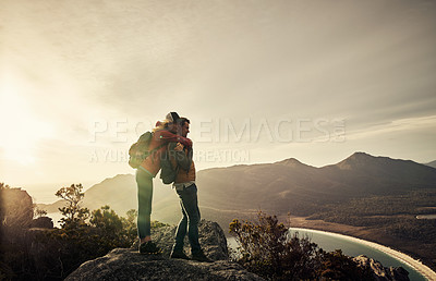 Buy stock photo Full length shot of an affectionate young woman embracing her boyfriend while hiking through the mountains