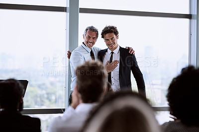 Buy stock photo Shot of a mature businessman introducing a colleague during a conference