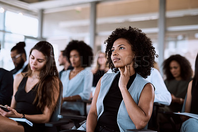 Buy stock photo Shot of a businesswoman listening intently during a conference
