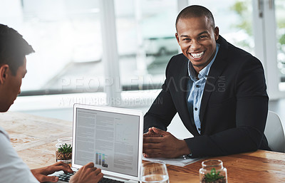 Buy stock photo Portrait of a young businessman working at a desk with a coworker in a modern office