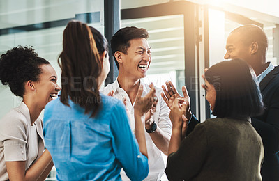 Buy stock photo Shot of a group of young businesspeople standing together and clapping in a modern office