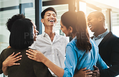 Buy stock photo Shot of a group of young businesspeople embracing each other in a modern office