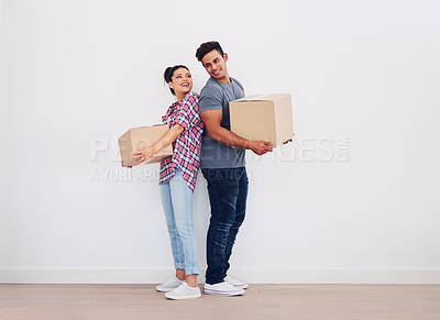 Buy stock photo Shot of a young couple holding boxes against a white wall