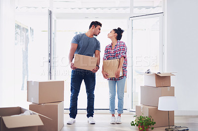 Buy stock photo Shot of a young couple moving into their new place