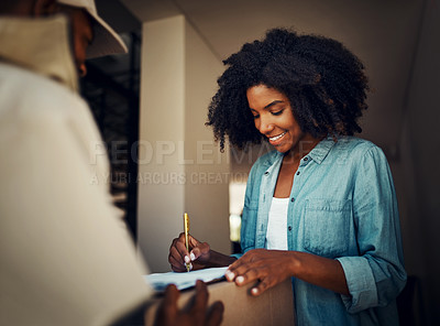 Buy stock photo Shot of a cheerful young woman signing a form after receiving a package from a delivery man at home during the day