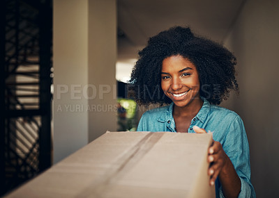 Buy stock photo Portrait of a cheerful young woman receiving a box while standing alone at home during the day