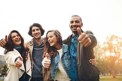 Buy stock photo Portrait of a group of cheerful young friends huddled together while showing thumbs up outside during the day