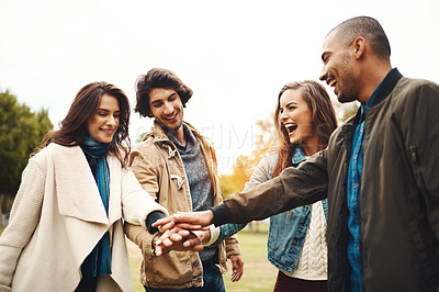 Buy stock photo Shot of a group of cheerful young friends forming a huddle with their hands together outside during the day