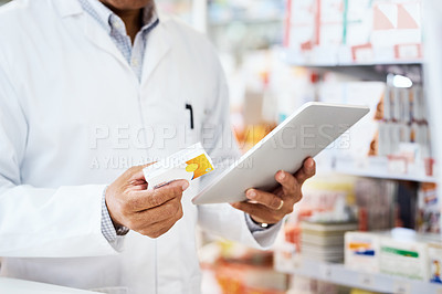 Buy stock photo Closeup shot of an unrecognizable pharmacist using a digital tablet in a chemist