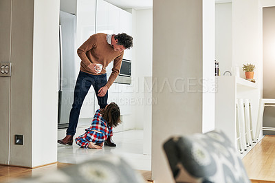 Buy stock photo Shot of an adorable little boy grabbing hold of his dad's leg and not letting go while being seated on the ground at home