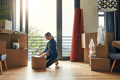 Buy stock photo Shot of a focused middle aged woman packing out a box at her new home inside during the day