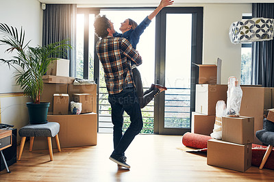 Buy stock photo Shot of a cheerful middle aged couple holding each other in excitement after moving into their new home inside during the day