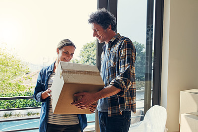 Buy stock photo Shot of a cheerful middle aged couple packing out a boxes at their new home inside during the day