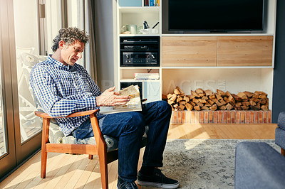 Buy stock photo Shot of a focused middle aged man seated on a chair while reading a book at home during the day