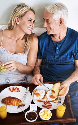 Buy stock photo Shot of an affectionate mature couple enjoying breakfast in bed at home