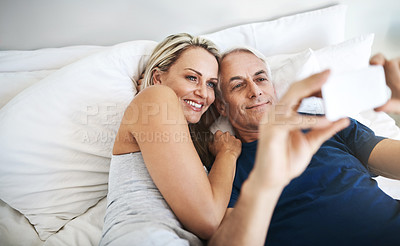 Buy stock photo Shot of an affectionate mature couple taking selfies in bed together at home