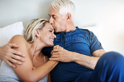 Buy stock photo Shot of an affectionate mature couple lying in bed together at home