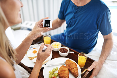 Buy stock photo Shot of a mature man gifting his wife with a pair of earrings and breakfast in bed at home