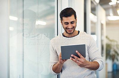 Buy stock photo Shot of a handsome young businessman using a digital tablet in an office