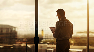 Buy stock photo Silhouette of a mature businessman standing in front of an office window and using a digital tablet