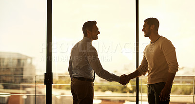 Buy stock photo Silhouette of two businessmen shaking hands in a modern office