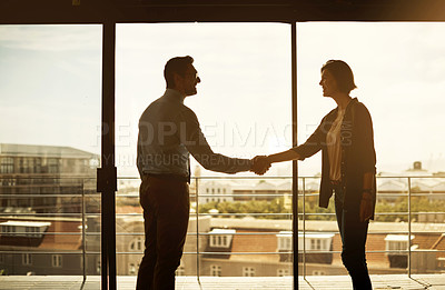 Buy stock photo Silhouette of a businessman and businesswoman shaking hands in a modern office