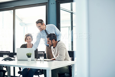 Buy stock photo Shot of a group of businesspeople using a laptop during a meeting in a modern office
